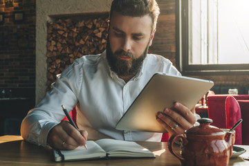 Young bearded businessman sits in cafe, home at table, holding tablet computer and writes in notebook. Man is working, student is studying. Online education, marketing, training.E-learning,e-commerce.
