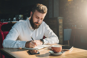 Young bearded businessman sits in cafe, home at table and writes in notebook. On table tablet computer, smartphone.Man is working, planning.Online education,marketing, training.E-learning, e-commerce.