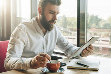 Young bearded businessman sits in cafe at table, uses digital tablet, drinks coffee.On desk is notebook, smartphone.Man working, studying.Online education, marketing, training. E-learning, e-commerce.