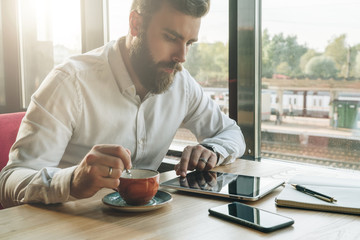 Young bearded businessman sits in office at table,uses tablet computer, drinks coffee.On desk is notebook,smartphone.Man working, studying.Online education,marketing, training. E-learning, e-commerce.