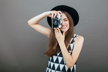 Stylish woman photographer with retro camera on the grey wall background. Image with copy space