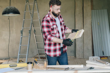 Young bearded businessman,builder,repairman,carpenter,architect, designer, handyman dressed in plaid shirt, goggles and gloves, stands in workshop and measures wooden bar.On table construction tools.