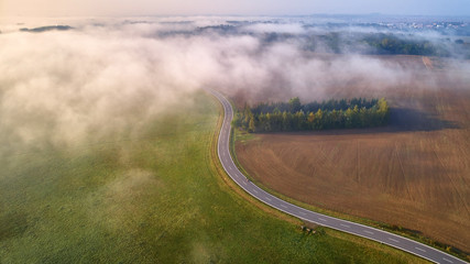 Aerial view on curved speed road, partly covered by fog. Curved road dividing landscape to brown and green half. Vertical view on rural countryside in autumn, foggy morning. Misty czech landscape.