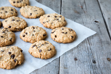 oatmeal cookies with chocolate on an old wooden background