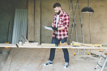 Hipster bearded man is carpenter, builder, designer stands in workshop, holds clipboard and takes notes. On desk is construction tools, in background stepladder. Repair, construction, carpentry.