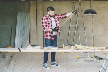 The man is a carpenter, a builder, a designer stands in the workshop, holds a roulette in his hands. Around there are construction tools, in the background a stepladder.