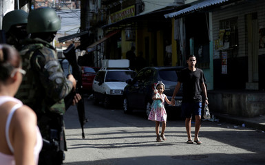Residents walk next to members of the armed forces in the Morro dos Macacos slum during an operation against drug gangs in Rio de Janeiro