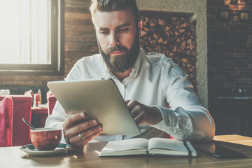 Front view.Young bearded businessman sits in cafe at table,uses digital tablet.On desk is notebook,cup of coffee.Man working,studying.Online education,marketing.E-learning,e-commerce. Instagram filter