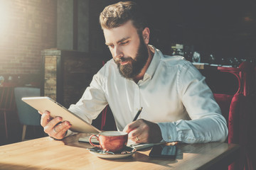Bearded businessman sits in cafe at table,uses tablet computer and writes in notebook.Man is working, student is studying.Online education,marketing,training. E-learning, e-commerce. Instagram filter.