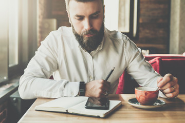 Young bearded businessman sits in cafe, office at table, holds pen in his hand,reads information on smartphone screen, drinks coffee.On desk is notebook. Online education, marketing. Instagram filter.