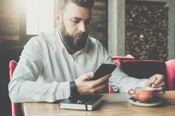 Young bearded businessman sits in cafe,office at table,reads information on smartphone screen, drinks coffee.On desk is closed notebook, pen. Online marketing, education, e-learning. Instagram filter.