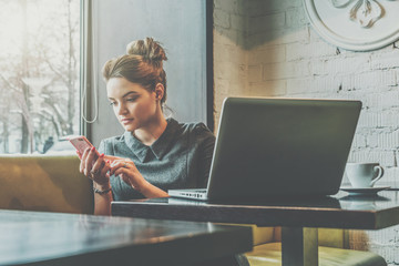 Young businesswoman sitting in cafe at table near window and using smartphone. On desk is laptop and cup of coffee. Girl working, learning online. Social media, network. Online marketing, education.