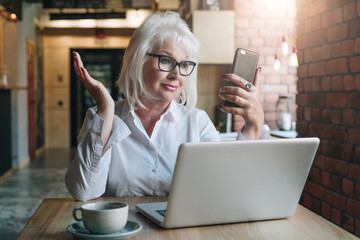 Smiling businesswoman is sitting at table in front of laptop and looking at smartphone screen in surprise. Education for adults. Pensioner works.Woman is chatting,blogging,checking email.Social media.