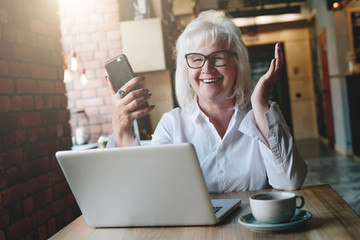 Happy businesswoman sitting at table in front of laptop, holding hands up and smiling, working, learning. In hands of women in a smartphone. Good news. Education for retired people. Online marketing.