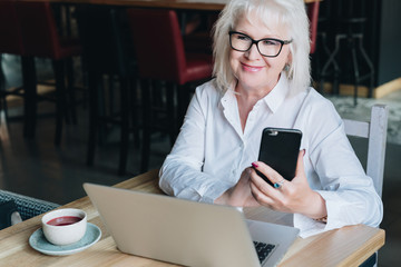 Smiling businesswoman dressed in white shirt is sitting at table in front of laptop and using smartphone. Freelancer working. Retired woman is chatting, blogging, checking email.Social media, network