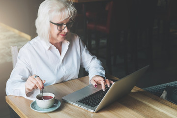 Smiling businesswoman in glasses sitting at table, working on laptop and drinking tea.Education for adults.Pensioner freelancer works.Woman is chatting, blogging, checking email.E-learning,marketing.