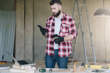 Man is carpenter,builder,designer stands in workshop, holds cup of coffee and uses smartphone. On desk is laptop and construction tools, in background a stepladder. Repair, construction, carpentry.