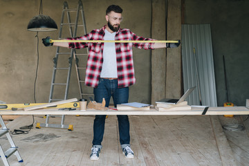 The man is a carpenter, a builder, a designer stands in the workshop, holds a roulette in his hands and looks at the laptop screen. Around there are construction tools, in the background a stepladder.
