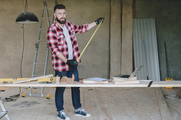 The man is a carpenter, a builder, a designer stands in the workshop, holds a roulette in his hands. On table laptop and construction tools, in background a stepladder.Repair, construction, carpentry.