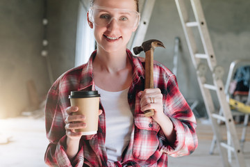 Front view. Portrait of smiling female construction worker, carpenter, repairman standing in workshop wearing safety glasses, holding hammer and cup of coffee in his hand.In background stepladder.