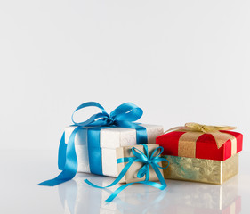 Three gifts boxes with ribbons on white