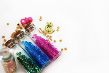 Tiny glass bottles filled with colorful beads and elements for a baby spilling out, isolated on white background with space for text.