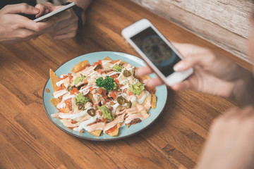 Taking a photo of homemade nachos with smart phone on wooden tab
