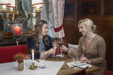 Two women toasting with wine in restaurant