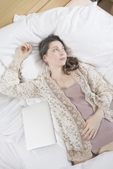 Woman with laptop relaxing in bed