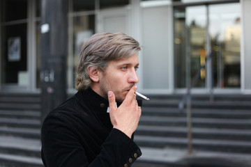 Portrait of a stylish man smoking cigarette in the street