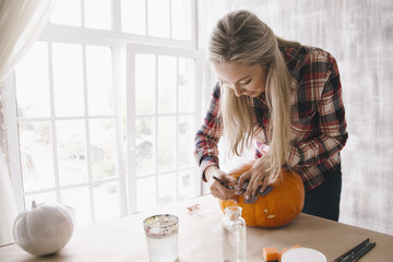 Woman decorating pumpkin using decoupage technique