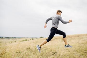 Fit Man in Sportswear Running  Outdoors