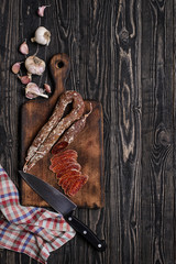 Chorizo, knife, garlic and napkin.Top view/Dried sausage, kitchen knife, napkin and garlic with chorizo pieces on rustic chopping board