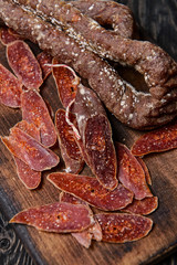 Dried chorizo sausage.Selective focus/Dried chorizo sausage and slices on a wooden cutting board