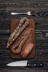 Dried sausage, knife and fork/Three types of dried sausages, knife, fork on wooden table.Top view