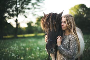 a girl cuddles her horse