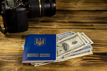 Traveling concept with  ukrainian passport, dollars and modern photo camera on wooden desk