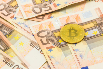 A symbolic coins of bitcoin on banknotes 50 Euro background. business concept.