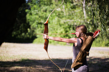 Woman taking aim with bow and arrow