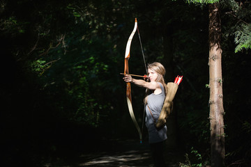 Woman aiming with archery in the wood