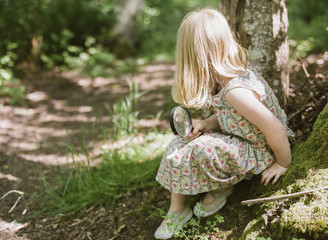 Young Girl Sits by a forest path with a spy glass