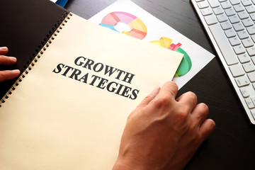 Businessman holding book with growth strategies.