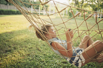 Blonde Girl Texting in a Hammock