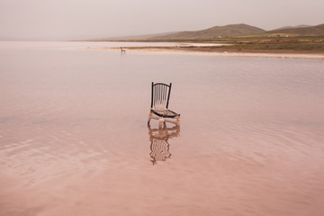 Broken chair in pink lake