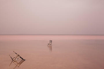 Broken chair in pink lake