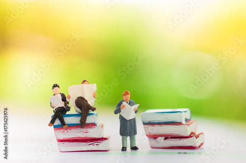 Miniature people sitting on the book using as background education or business concept