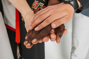 People of different nationalities and religions hold hands. The concept of friendship among peoples. The concept of friendship, communication, teamwork, education, recruitment.