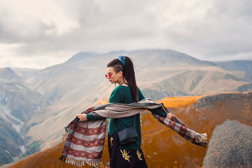 portrait of a young beautiful hipster girl in sunglasses with hair dreadlock in a boho gypsy hippie style clothes on a background of cloudy sky and autumn mountains of Georgia dancing