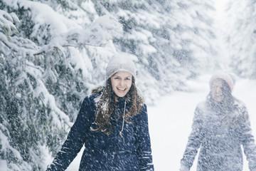 Joyful girlfriends having fun in the snow