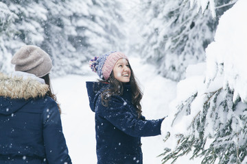 Two happy young female friends enjoying winter